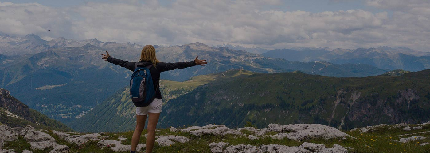 woman standing on top of mountain with arms outstretched