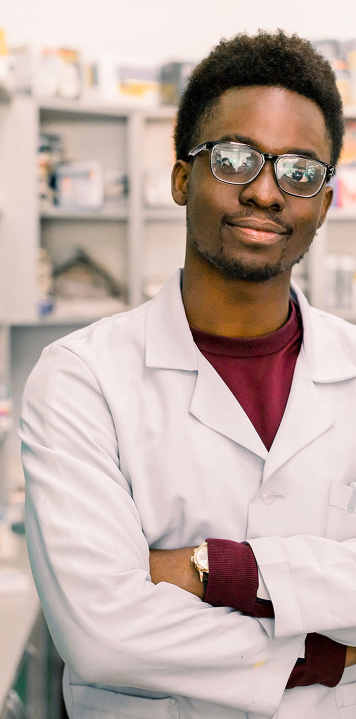 man with arms crossed in lab coat and glasses
